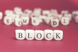 Block word written on wood cube with red background