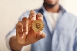 Blockchain. African-american man holding golden bitcoin in hand