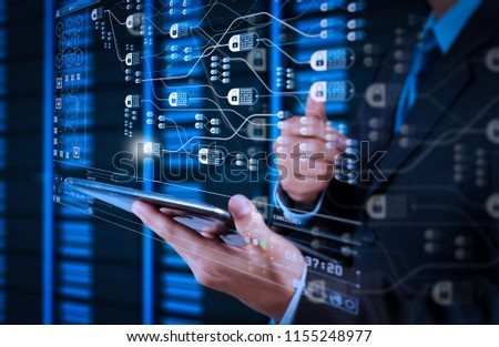 Blockchain technology concept with diagram of chain and encrypted blocks.businessman hand using tablet computer and server room background #1155248977