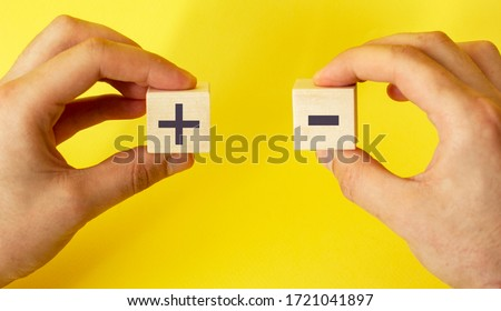 blocks in hands on a yellow background with plus and minus Stockfoto ©