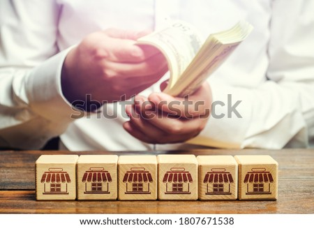 Blocks symbolizing business network and businessman counting money. Building a successful business empire. Expansion and competitive growth. Franchise concession concept. High return on investment. Сток-фото ©