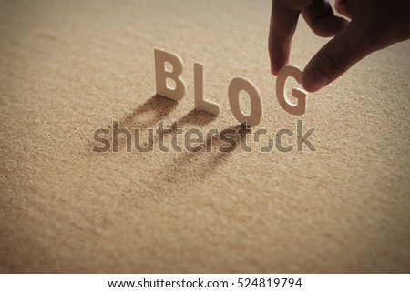 BLOG wood word on compressed board with human's finger at G letter
