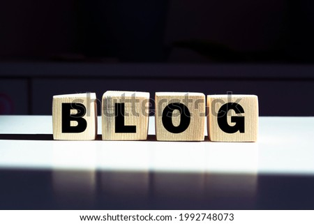 BLOG word written on wood cubes. Wooden blocks on blue background. Social media. Blogging and business concept.
