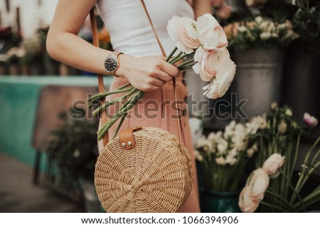Blogger girl holding a bunch of flowers at the flower market. Blogging concept.