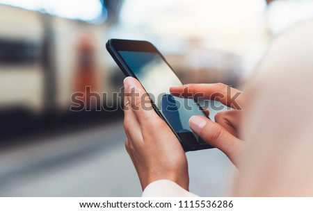 blogger hipster using in hands gadget mobile phone, woman texting message on blank screen smartphone, texting message, mockup online wifi internet concept, hipster waiting on station platform on back