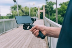 Blogger in nature shoots video on a smartphone with a manual camera stabilizer