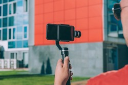 Blogger in the city shoots video on a smartphone with a manual camera stabilizer