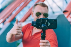 Blogger in the stadium shoots video on a smartphone with a manual camera stabilizer