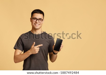 Blogger insists at better offer for customers. Happy handsome millennial guy in brown t-shirt and glasses, points finger at mobile phone with blank screen advertising app, isolated on beige background Stock photo ©