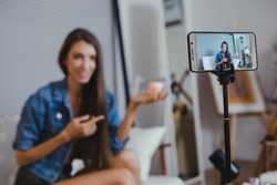 Blogger of caucasian woman with review product and talking camera live recording video on social network at home. Online merchants selling cosmetics on social media via mobile phones.