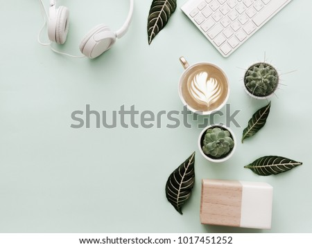 Blogger Pastel Background With Coffee Cup, Headphones and botanical elements. Flat Lay