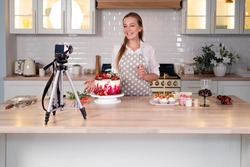 Blogger pastry chef makes a video lesson about cooking a cake. young woman in an apron at home in the kitchen tells the recipe on camera. Online broadcast, author leads a blog or course about cooking