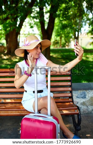 Blogger woman in straw hat and removed mask holds on her head, in the park