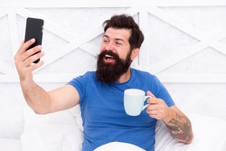 Blogging from bed. Happy blogger drink coffee in morning. Bearded man keep real time live blog. Keeping private personal blog. Making new blog post from smartphone. Online social network. Weblog.