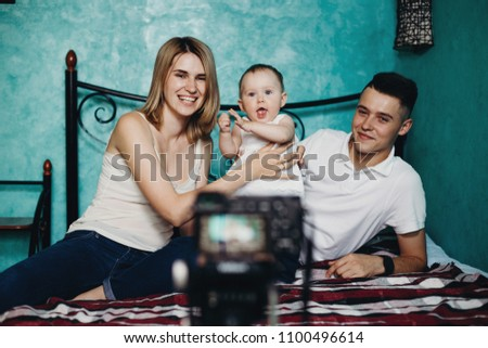Blogging, social media, mother blogger. Happy family with baby daughter recording a video for blog. Parenting, family, modern parents, childhood, parenthood concept