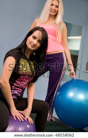 Blond and brunette women in fitness center