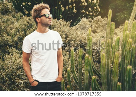 Blond attractive hipster guy  wearing white empty t-stirt and  sunglasses is standing in the garden near a big cactus next to his bike. #1078717355