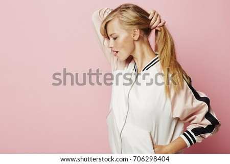 Blond babe holding ponytail in pink studio