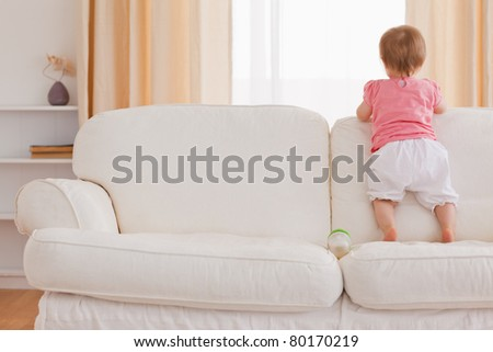 Blond baby standing on a sofa in the living room