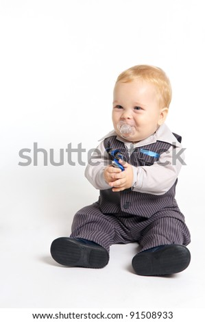 blond baby with pacifier in formal suit