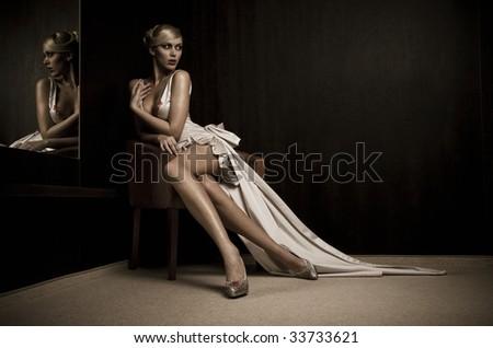 Blond beautiful woman beside mirror