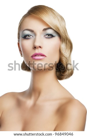 blond beautiful woman with strong make up and an old fashion hair stylish in beauty portrait close up. She is in front of the camera and looks in to the lens with mouth slightly open.