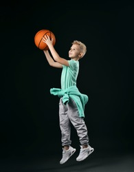 Blond boy in green t-shirt, pants, sneakers and hoodie around waist jumps throwing the basketball ball over dark background. Trendy sports active children fashion concept