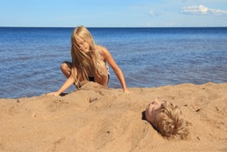 blond boy is buried in the sand on the beach. Eyes closed. girl next to her buries her brother.