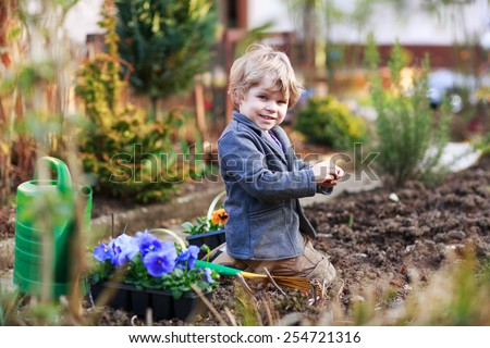 Blond boy of 2 years having fun with gardening and planting vegetable plants and flowers in garden, outdoors. Active leisure with kids, learning gardening and environment.