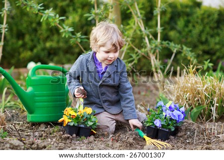 Blond boy of 2 years having fun with gardening and planting vegetable plants and flowers in garden, outdoors