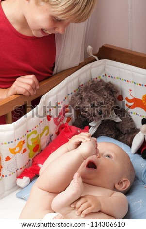 Blond boy with his newborn baby brother indoor - stock photo