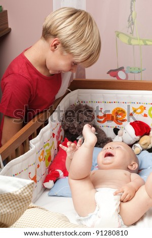 Blond boy with his newborn baby brother indoor