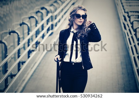 Blond business woman in sunglasses walking on city street. Stylish fashion model outdoor #530934262