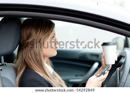 Blond businesswoman sending a text while driving to work