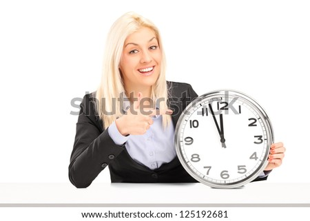Blond businesswoman sitting and pointing on a wall clock, isolated on white background