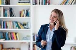 Blond businesswoman with blazer at phone at office of company