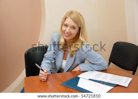 blond  businesswoman with pen at the office desk indoor smiling