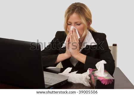 Blond caucasian woman wearing business attire sitting in front of laptop computer with a box of tissues blowing her nose