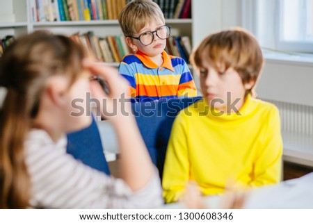 Blond caucasion boy kid in eyeglasses with sadness emotion sitting in classroom, his classmates talking on foreground in kindergarten preschool or primary school. Bulying depression concept Stock fotó ©