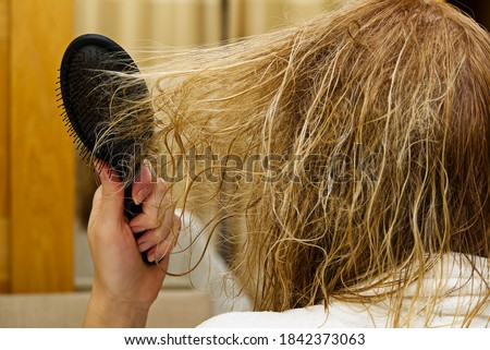 blond combing wet and tangled hair. Young woman combing her tangled hair after shower, close-up. Foto stock ©