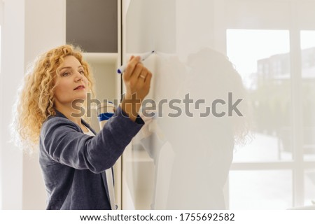 Blond curly business woman or teacher writing in flipchart. Close up, side view, copy space text. Female preparing a presentation in a conference or meeting setting.