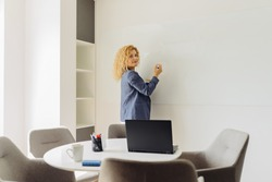 Blond curly business woman or teacher writing in flipchart. Gorgeous single female business woman or instructor holding an erasable marker in hand at white board in empty meeting room Copy space text.