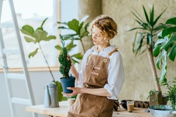 Blond curly woman gardener housewife in apron forming thuja tree using garden shears at home. Find time for yourself concept.