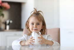 Blond cute baby girl with blue eyes with traces of milk on the lips is holding a glass of milk siting at a white table in a white kitchen. Milk for good health