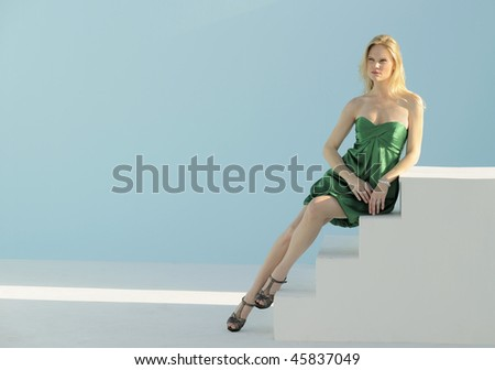 Blond fashion model wearing green party dress leaning on white steps in a shaft of sunlight.