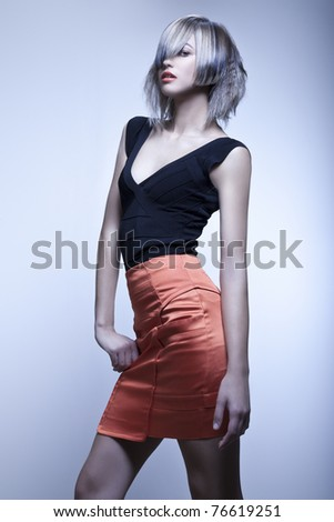 Blond fashion model with modern haircut and red skirt in studio with blue background