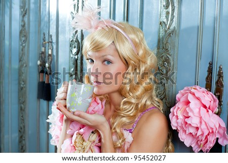 blond fashion princess woman drinking tea or coffee at home with vintage pink dress