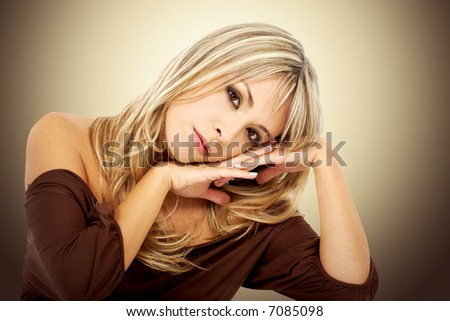 blond fashion woman portarit leaning on a table with her hands by her face