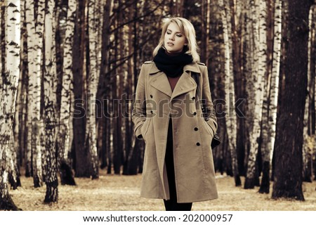 Blond fashion woman walking in autumn forest  - stock photo