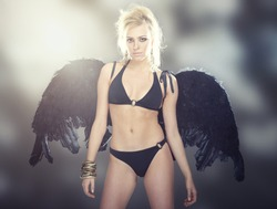 Blond female angel with black wings on abstract background